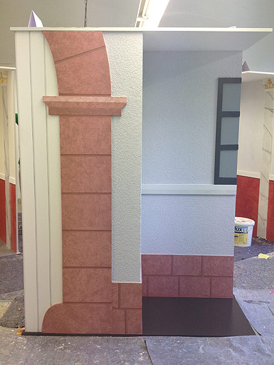 Bild 1: zeigt die Fassade. Torbogen und Sockel bekamen eine Steinimitation, Links wurden die Schattenfugen eines Holztores imitiert. Die Fassadenfläche wurde mit einem 2mm Kratzputz verputz und rechts sieht man einen Fensterladen in zweifarbiger Pinsellackierung.