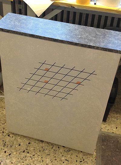 """Bild 4: ist ein Aktenschrank. Dieser wurde im Spritzverfahren mit einer Folientechnik gestaltet. Das Logo wurde mit Folie und verschiedenen Blattmetallen (Silber, Kupfer) dargestellt. Die """"Arbeitsplatte"""" bekam eine Marmorimitation mit einem Naturschwamm und Dispersionsfarben."""