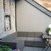 Die Symbiose einer rustikalen historischen Wand mit modernen Bauelementen machen diese Dachterrasse zu einer Wohlfühloase.